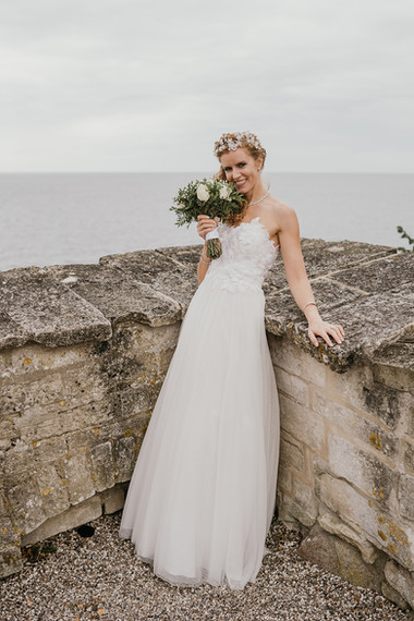 A lovely bride smiling and holding her bouquet during her Denmark elopement to Stevens Klint, one of the many wedding packages abroad for two we offer.