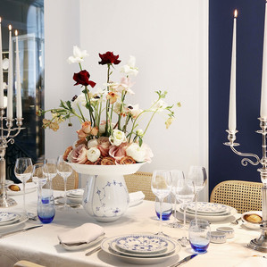 A table set-up with lovely plates and a rose centerpiece at the Vindeholme Castle, a small castle wedding venue.
