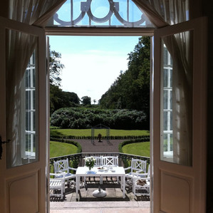 A sitting area outside of the Vindeholme Castle overlooking the green, majestic courtyard, a lovely castle to get married in Denmark.