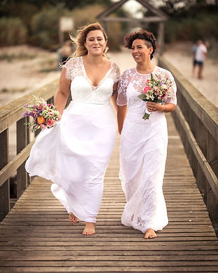 Two brides walking down the pier in a Nordic beach during their same sex marriage in Denmark.