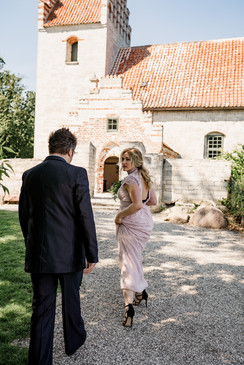 Husband and wife walking towards the Old Hojerup church during their adventure wedding at Stevens Klint, one of the best places to get married abroad in Denmark.