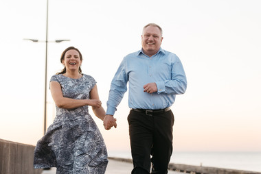 A couple kissing and dancing by the Nordic pier in Lokken after they renewing their vows abroad
