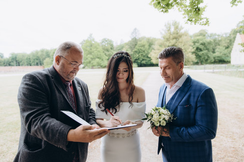 Recently married, a couple signing off on their wedding documents on a romantic wedding location near a castle as they get married in Denmark