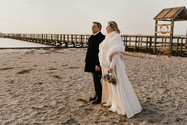 A husband and wife holding hands and looking out at the horizon by the Hestehoved Jetty at Lolland Island, enjoying their winter elopement abroad.