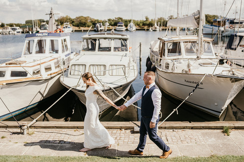 Newlyweds embracing at the marina in Lolland island on a sunny day, while on getting married in Denmark