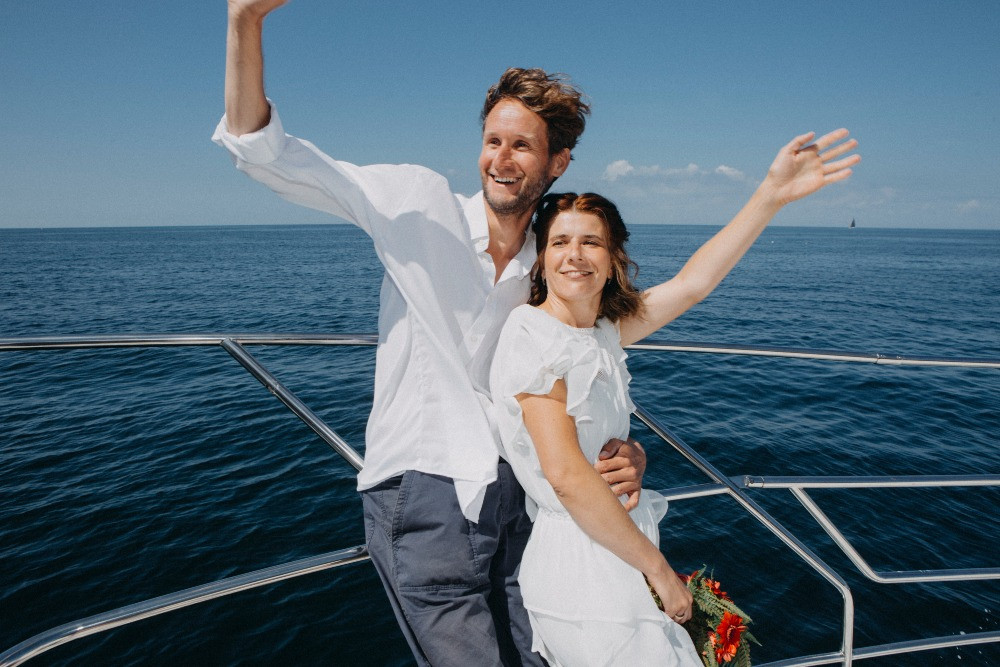 happy newlyweds greet everyone from the boat where they enjoy adventure elopement wedding
