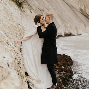 A couple embracing each other on Mon's Klint, enjoying their Danish island wedding in November.