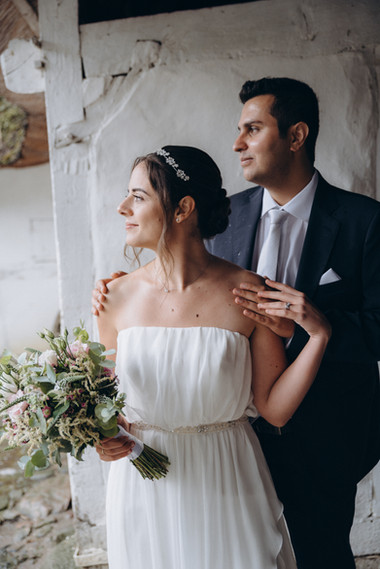 Newlyweds looking out into the horizon from the barn while on their wedding abroad, making their marry abroad idea of a green eco-style wedding come to life with one of our elopement packages for two.