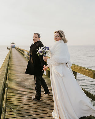 A couple smiling at the Hestehoved Jetty during their winter wedding by the beach in Denmark.