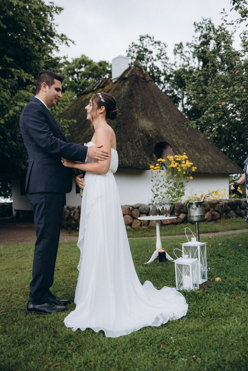 A couple still feeling romantic and happy even as rain sprinkles on their wedding day in a romantic location booked by one of our Denmark wedding packages.