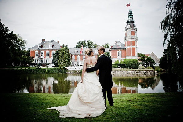 A couple eloping abroad, enjoying their photoshop with an adventure wedding photographer at Hvedholm castle.