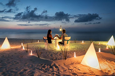 A romantic moment at a dinner set up with candles at a Nordic beach, a great vows renewal idea for a special occasion abroad.