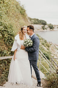 Newlyweds embracing on the cliffs during their adventure elopement in Denmark