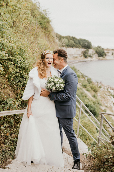 A couple rejoicing and hugging during their natural Denmark wedding venue adventure, one of the many destinations we offer in our elopement packages.