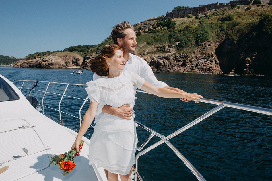 A groom holds his bride by the waist during their intimate wedding on a yacht in Вenmark