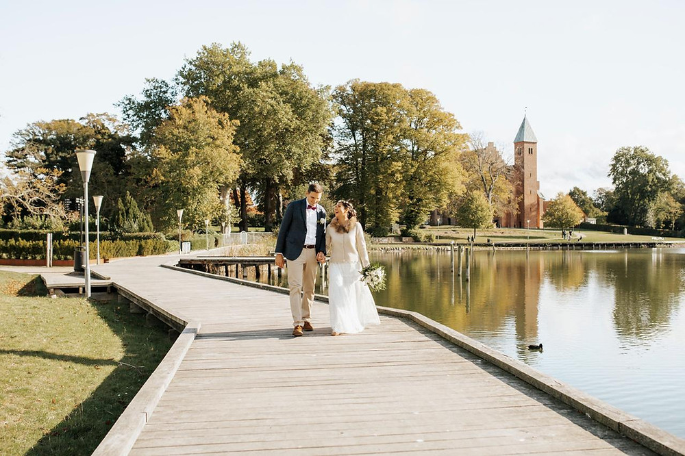 Newlyweds walking on the pier in Maribo, the wedding town in Denmark for foreign couples