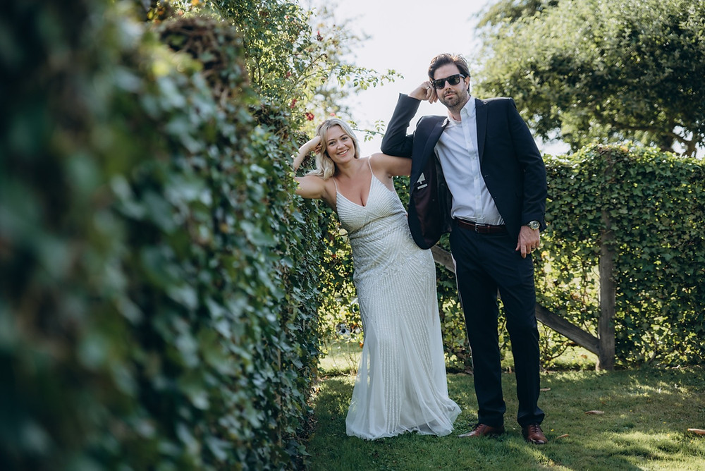 A couple landing back and smiling in the garden during their adventure wedding in Denmark