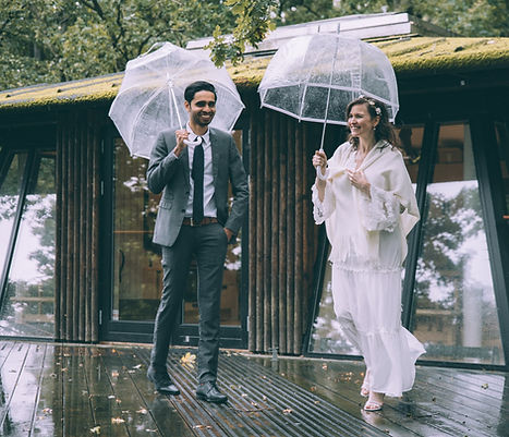 A couple posing during their elopement abroad made possible with an all-inclusive wedding package for two, posing at a treehouse with umbrellas where they had their adventure wedding.