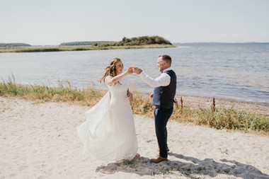 Husband and wife dancing after their beach wedding ceremony in Lolland Island by the Hestehoved Jetty after booking our Denmark elopement package