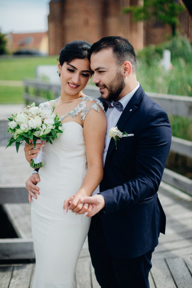 Newlyweds after their marriage in Denmark keeping the white wedding bouquet