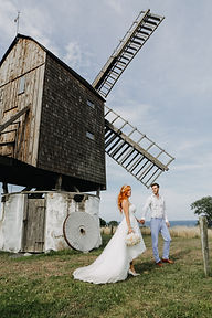 Newlyweds halding in hands in the front of the old mill on Bornholm island - destination for the couples eloping abroad