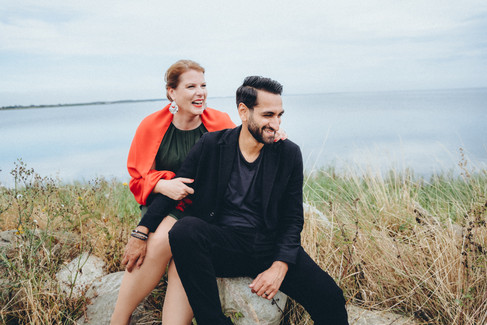 A couple sitting by the rocks and grass, posing by the sea and smiling while they renew vows abroad