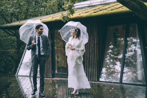 Newlyweds holding umbrellas during a romantic Scandinavian wedding adventure elopement.