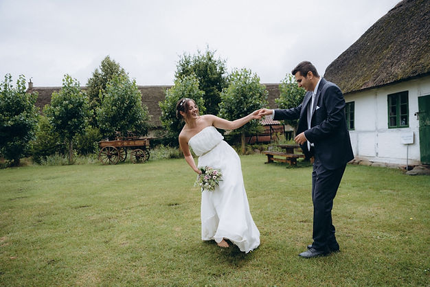 A couple holding hands and having fun during their green wedding in Denmark.