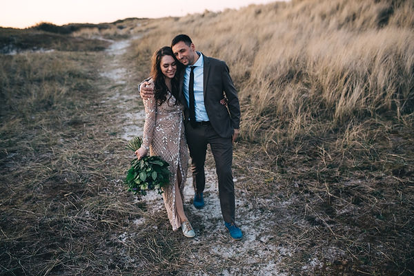 A stylish couple walking through a grassland in Denmark as they embrace and smile while they renew wedding vows abroad.
