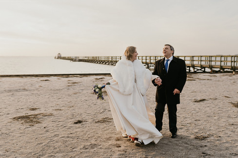 Newlyweds at the Hestehoved Jetty on Lolland Island as they enjoy their small winter wedding in Denmark