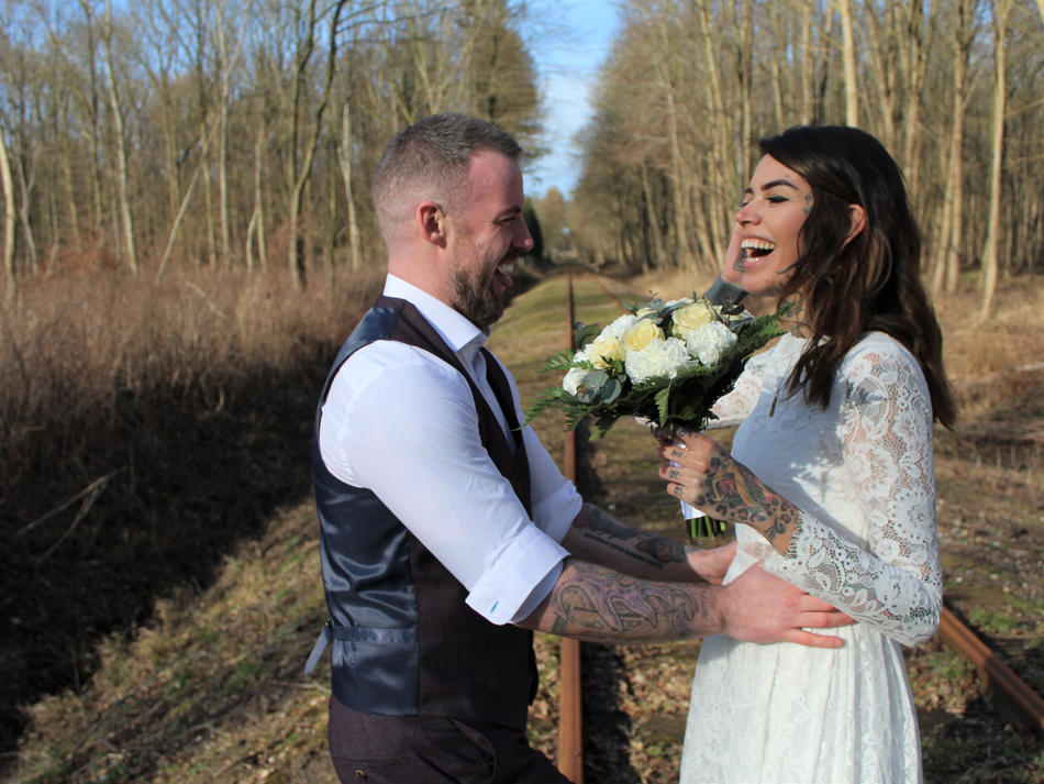 Laughing and holding each other, a couple gets married in a mysterious forest in Denmark, choosing the Scandanavian outdoors as their destination wedding venue.
