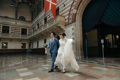 A groom and his bride walking enthusiasticaly through the corridors of the town hall during their  Copenhagen City Hall wedding.