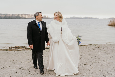 A couple holding hands and walking by the waterfront on Lolland Island during their winter wedding as they get married in Denmark.
