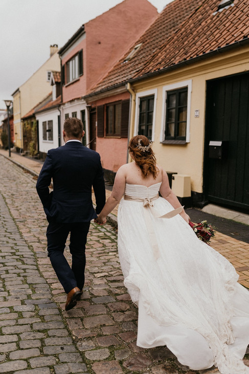Newlyweds holding hands and walking through Maribo in Lolland Island after their intimate wedding in Denmark abroad for two.