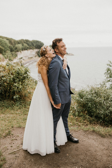 A wife hugging her husband laughing and smiling while they look out towards the horizon and the Baltic Sea during their adventure elopement to Denmark, making their idea of a Nordic wedding come true.