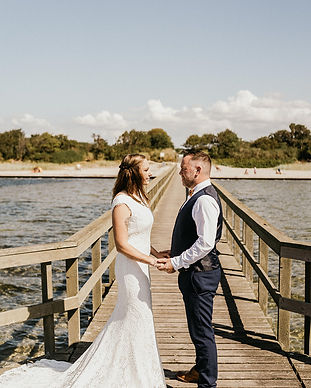 A couple holding hands at the Hestehoved Jetty on Lolland Island during their wedding island adventure in Denmark.