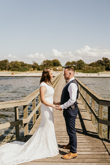 Newlyweds holding hands at the Hestehoved Jetty during their beach wedding in Lolland Island, offered with our Denmark elopement packages.