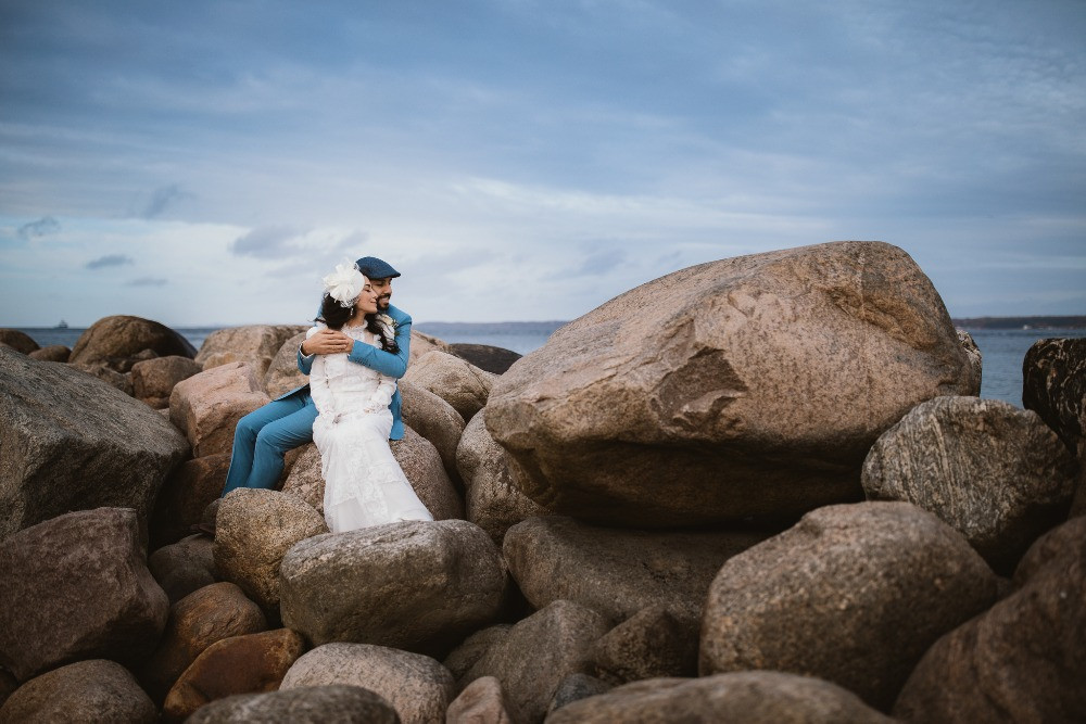 Couple sitting on the rocks after they got married in the Danish castle Elsinore