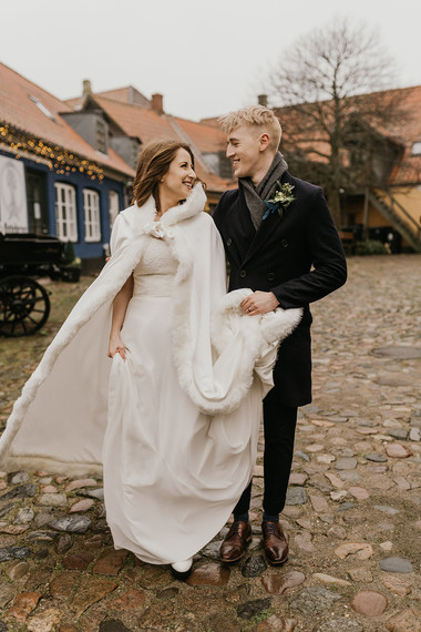 Newlyweds laughing and looking into each other's eyes as they explore the picturesque towns of Mon Island during their winter elopement to Denmark for their Nordic wedding