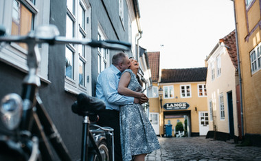 A husband hugging and kissing his wife on the neck while they renew their wedding vows in Denmark.