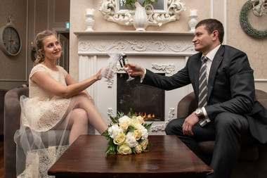 Newlyweds toasting champagne by the fireplace at the Bandholm Hotel in Denmark after their adventure wedding ceremony