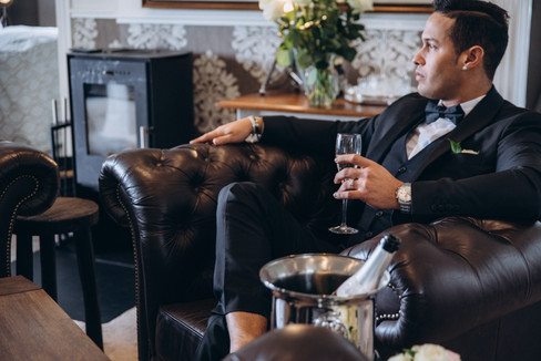 A portrait of a groom holding champagne and sitting in a hotel lounge area in Maribo on Lolland Island during his Denmark wedding, a great wedding venue for intimate weddings abroad.