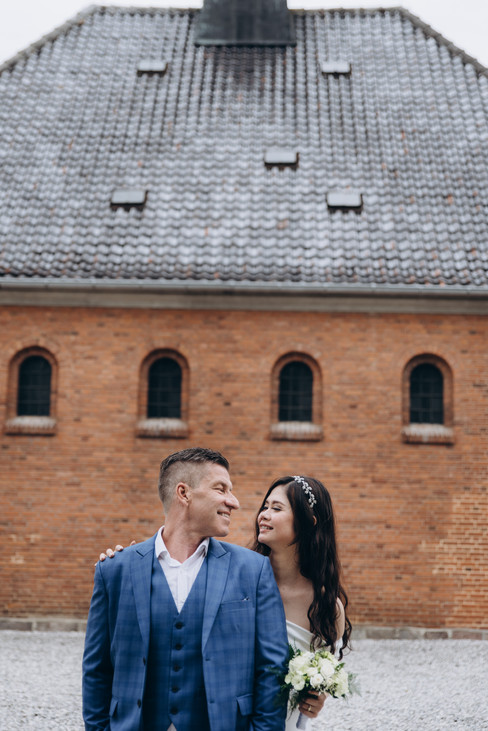 A couple looking into each other's eyes and smiling during their castle wedding adventure in Denmark.