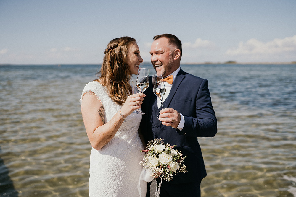 Linn & Thomas enjoying glass of champagne after their beach wedding in Denmark