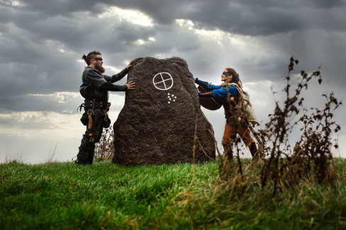 Man and wife touching a large historical rock during their wedding abroad in Denmark, one of the best places to get married abroad in Europe.