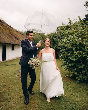 A groom holding an umbrella for his smiling bride as they enjoy their open-air museum marriage in Denmark
