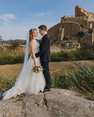 Newlyweds embracing by the Hammershus Ruins on Bornholm Island as they enjoy their adventure wedding at the Baltic Sea, one of the best places to elope abroad.