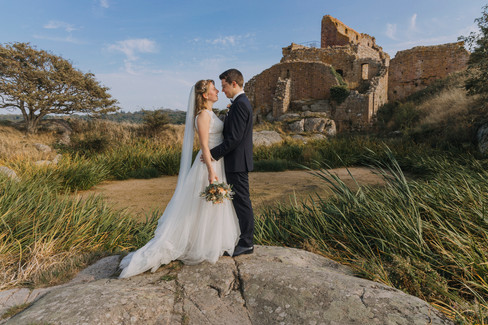 A couple hugging and gazing into each other's eyes at the Hammershus Ruins on Bornholm Island, a perfect marry abroad idea for Scandinavian weddings.