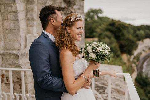 A groom hugging his wife during their intimate wedding abroad, pictured at the ancient church overlooking the Baltic sea, a dreamy Denmark wedding venue.