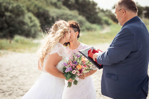 A lesbian couple kissing during their bohemian wedding in Denmark, a great same-sex wedding idea